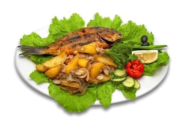 Дорада, запеченая с картофелем, петрушкой, чесноком и пекорино.